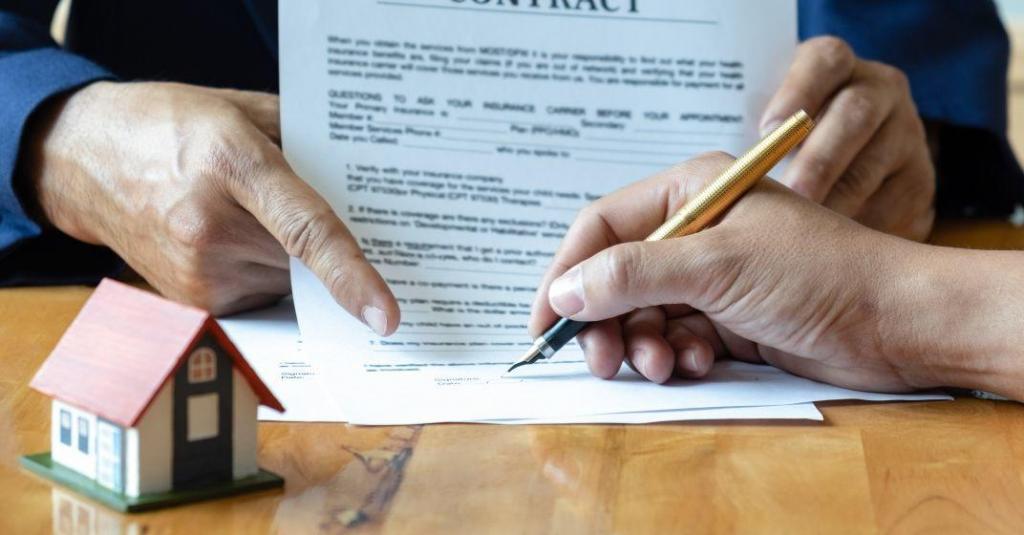 Člověk podpisuje nájemní smlouvu na dům