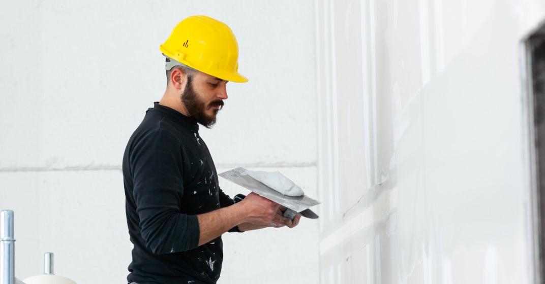 Dělník opravuje roh zdi