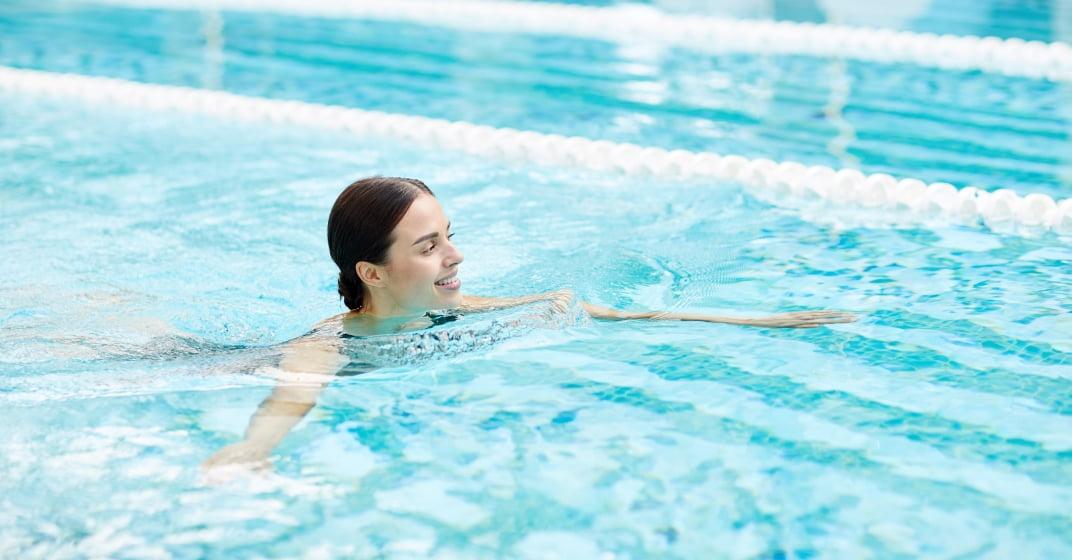 Žena plave v bazénu